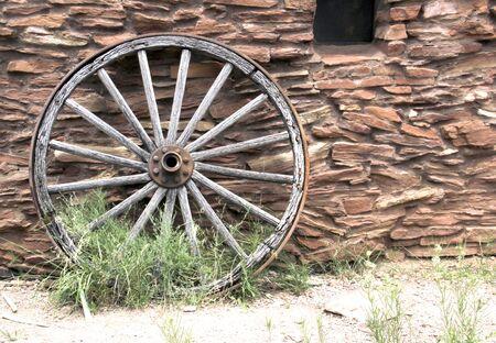 carreta madera: Rueda de carro de madera de la vendimia con una piedra construido edificio que el fondo, Foto de archivo