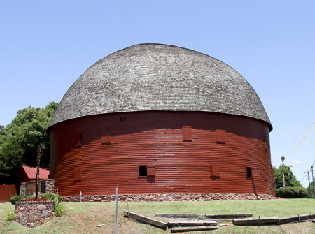 restored: Red restored round barn against a blue sky background