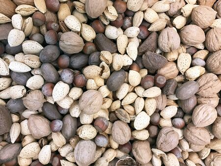 Several varieties of mixed nuts make a snack food background