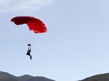 Parachute jumper in a red chute floating back to earth Stock Photo