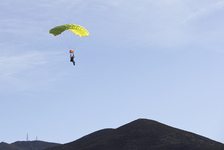 Parachute jumper with a yellow chute returning to earth with blue skies in the background