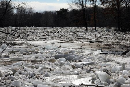 ice dam: Flood waters send chunks of ice down a river Stock Photo