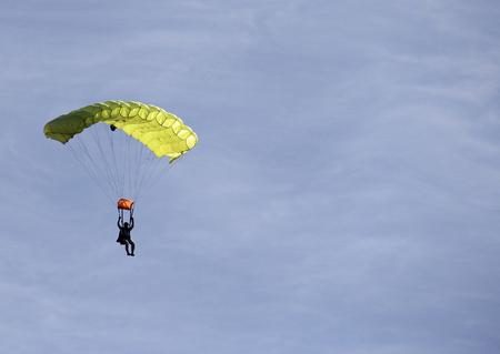Man in a yellow parachute floating back to earth