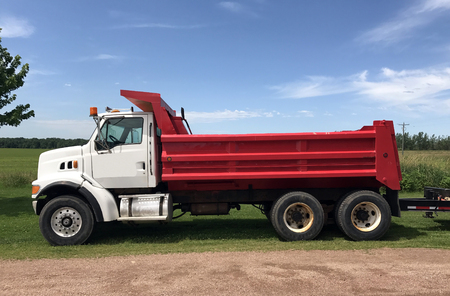Red and white dump truck against a blue summer sky Stock Photo