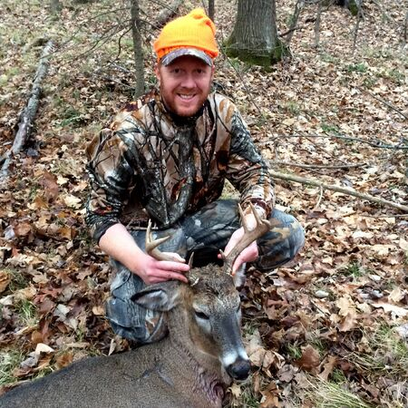 Happy hunter with an eight point Whitetail Buck harvested in a Wisconsin gun season Фото со стока