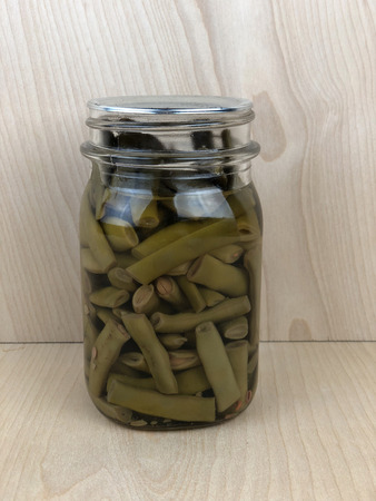Pint jar of pickled garden beans against a wooden background