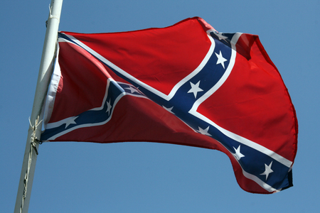 Confederate flag flying at half mast against a blue sky background