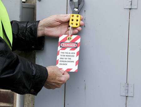 electrician locks out an electrical panel with a tag out sign.