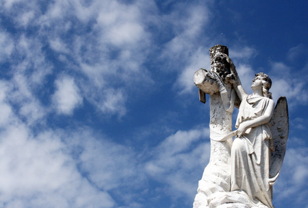Cemetery statue of an Angel and a cross looking to the sky