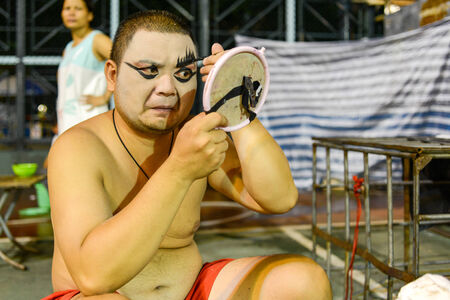 Hong Kong, China - August 18, 2014  A traditional opera actor is making up at the back stage of a traditional tea house in hongkong, China  Generally, an actor needs 30 - 60 minutes to complete the whole process