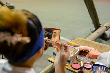 stage make up: Hong Kong, China - August 18, 2014  A traditional opera actor is making up at the back stage of a traditional tea house in hongkong, China  Generally, an actor needs 30 - 60 minutes to complete the whole process