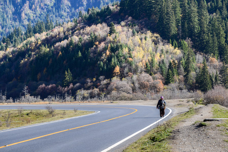 non marking: Jiuzhaigou, Sichuan, China - November 05, 2014 : Old woman take his herbal medicine on the highway roadside.