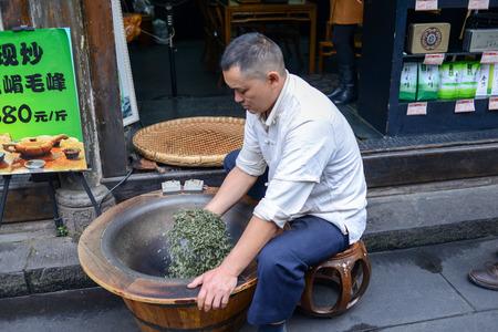 evaporarse: Sichuan, China - 05 de noviembre 2014: Hombre chino Tea Revolver-secado, utilizados en el proceso de hacer el t� en la olla para hacer atrofia t� microllama manera marchitan, hacer t� rod� a trav�s del agua artificial evapore r�pidamente, bloqueando el proceso de fermentaci�n del t�