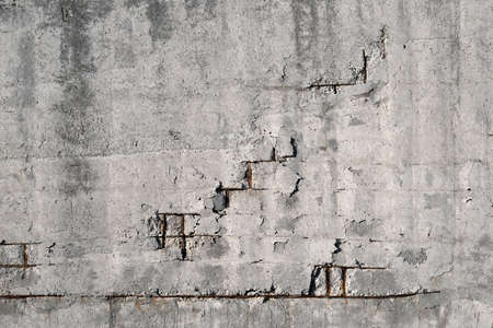 An old cracked concrete wall with rusty rebar