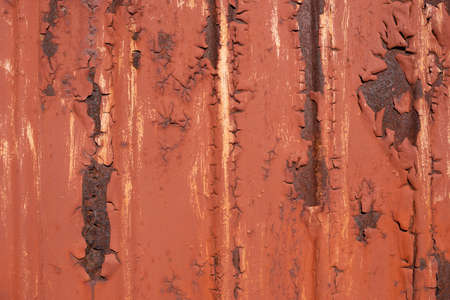 Cracked red paint on a rusty corrugated metal panel