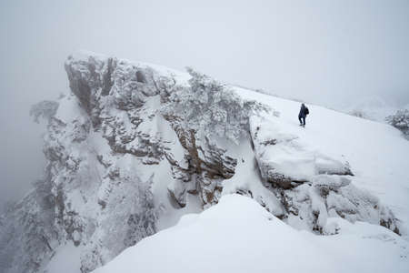 One man walks along the cliff to the top in the snowy misty mountains