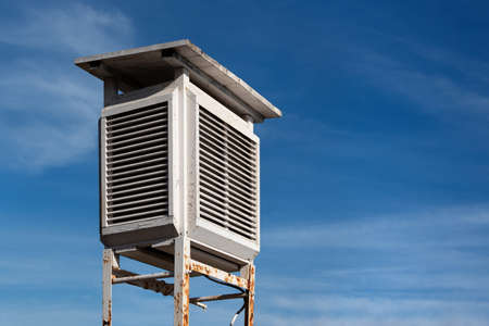 Old- school battered white wooden weather station with blue sky clouds background