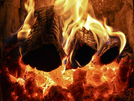 A fireplace with burning logs, red coals and fire photo