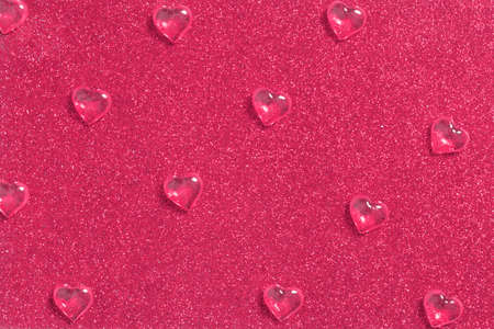Crystal drops of glassy hearts on shiny glitter background