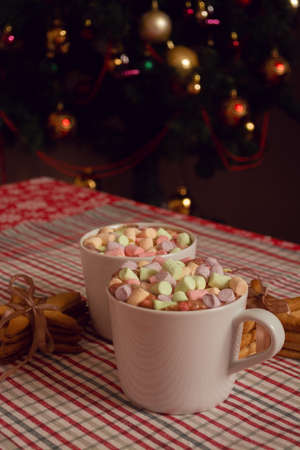 White mugs of hot chocolate beverage with colorful marshmallow and star shaped gingerbread cookies on Christmas tree background