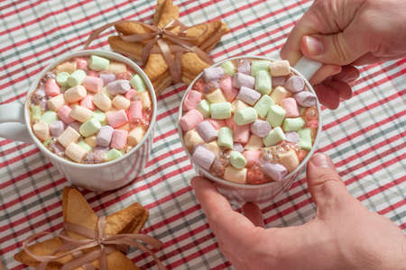 Hot chocolate beverage with colorful marshmallow holding by male hands Archivio Fotografico - 138045978