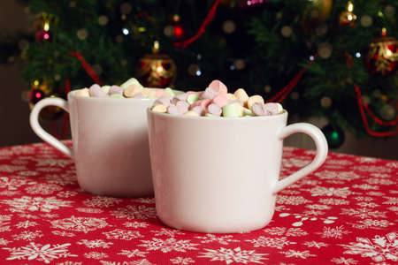 White mugs of hot chocolate beverage with colorful marshmallow on red cloth table with snowflakes on Christmas tree background Archivio Fotografico - 138045895