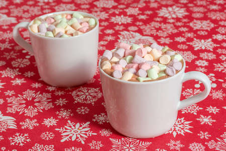 White mugs of hot chocolate beverage with colorful marshmallow on red cloth table with snowflakes Archivio Fotografico - 138045983