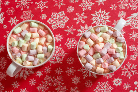 Top view of colorful marshmallow in hot chocolate drinks in white mugs on red snowflakes background