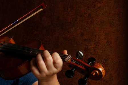 Child hands holding violin and playing symphony. Kid violinist playing music concept