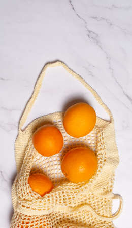 Eco friendly crochet shopping bag with oranges on marble background with copy space. Zero waste food shopping concept. Plastic free items for stop pollution. Sustainable lifestyle concept 版權商用圖片