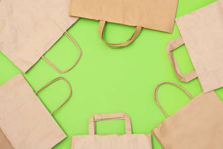 Craft paper recyclable bags on green background with copy space for your text. Zero waste shopping and plastic free concept