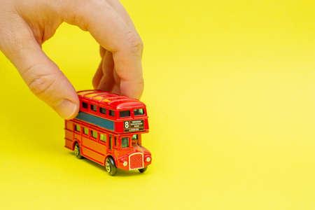 Britischer roter Spielzeug-Doppeldeckerbus, der von männlicher Hand auf gelbem Hintergrund fährt. Konzept des Englischunterrichts und Verbesserung der Sprech- und Sprechfähigkeiten