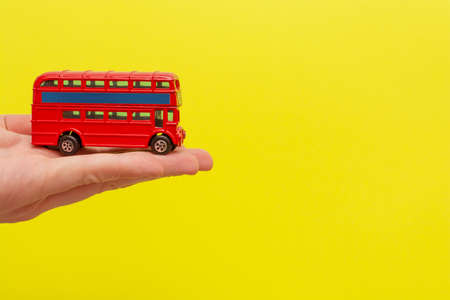 British toy double-decker red bus holding by male hand on yellow background with copy space for your text. Concept of English language lesson