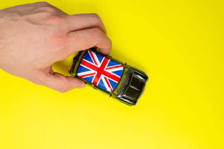 Classical English cab with british flags on the roof on the yellow background. English language lesson concept. Abstract symbol of improving and boosting language skills