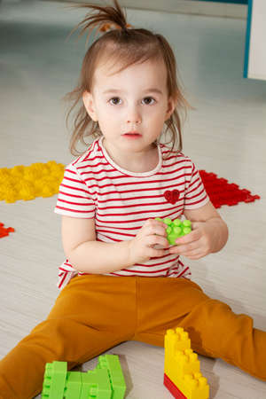 Portrait of a little Caucasian girl with colorful constructor block sitting on the floor