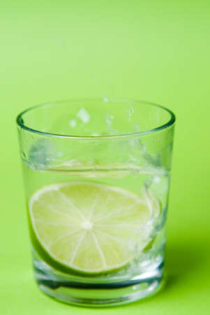 Slice of lime in a water glass against a green background