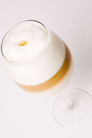 Latte macchiato with layers in the wine glass in a diagonal position