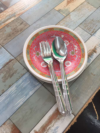 style: Chinese style spoons, forks, and dishes on a wooden table.