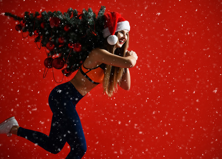 Christmas fitness sport woman wearing santa hat holding xmas tree on her shoulders. running forward on a snowing red background