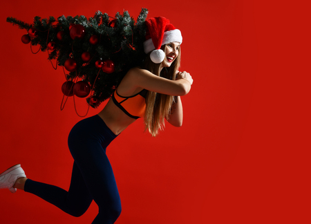 sexy Christmas fitness sport woman wearing santa hat holding  xmas tree on her shoulders. running forward on a red background