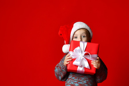 Funny smiling joyful  child boy in Santa red hat holding Christmas gift in hand and hide behind the gift over the red background Stock Photo