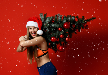 sexy Christmas fitness sport woman wearing santa hat holding xmas tree on her shoulders. running forward on a red background Stock Photo
