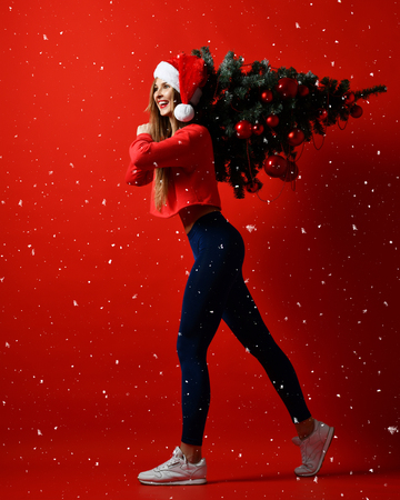 sexy Christmas fitness sport woman wearing santa hat holding  xmas tree on her shoulders. running forward on a red snowing background