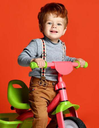 Porträt eines süßen, schönen rothaarigen Jungen auf dem Fahrrad über einem isolierten orangefarbenen Hintergrund