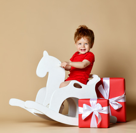 little cute red-haired toddler boy sits astride a rocking horse and a pile of a pile of gifts, studio shot, happy baby. smiles