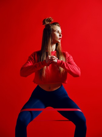Woman with good physique doing stretching work out with elastic bands. Sports girl in fashionable sportswear on red background. Strength and motivation. Stock Photo