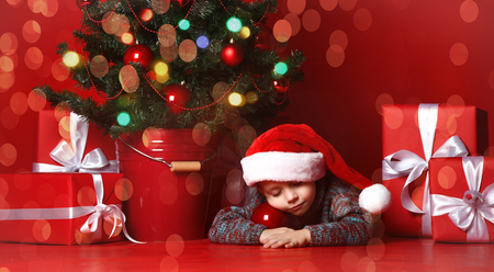Cute little boy sleeping  next to the Christmas tree, he is waiting for Santa Claus, Christmas and holidays concept