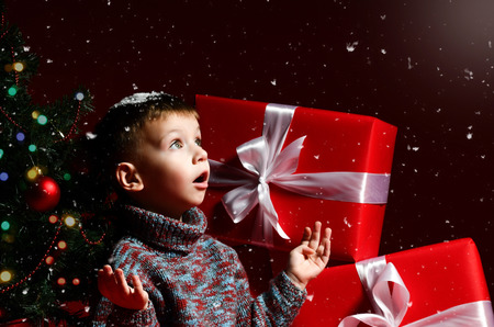 A surprised little boy on New Year's Eve and Christmas is sitting under the Christmas tree and looking at the snowflakes falling on his palms, waiting for a miracle and magic on the eve.