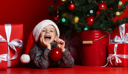 Happy xmas and New Year. Portrait of child in Santa red hat waiting for Christmas gifts. Little toddler boy lies under the Christmas tree with gifts and holds the Christmas ball.