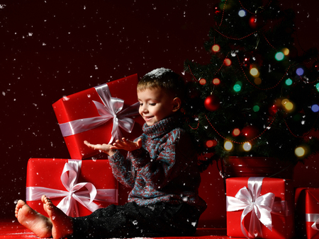 A little boy on New Year's Eve and Christmas is sitting under the Christmas tree and looking at the snowflakes falling on his palms, waiting for a miracle and magic on the eve. Stock Photo
